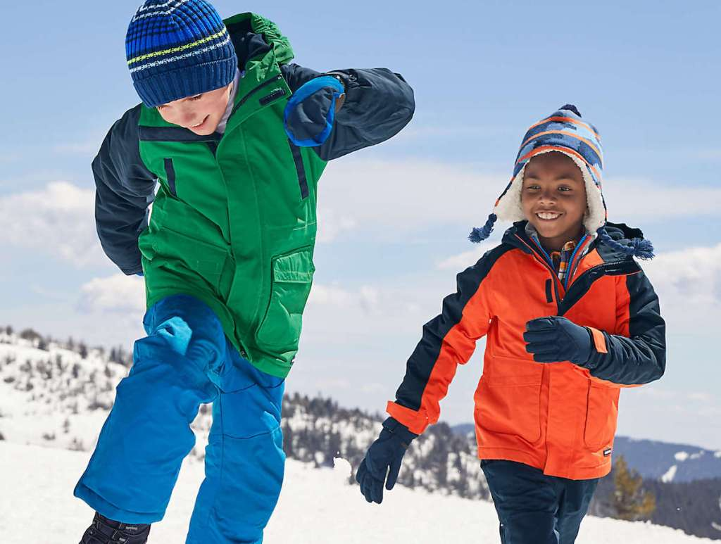 two boys playing in the snow wearing green and orange coats