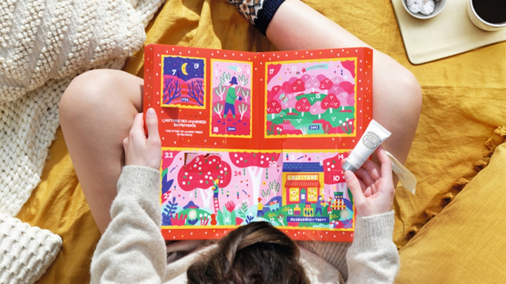 hand holding bottle of lotion with beauty advent calendar on girls lap