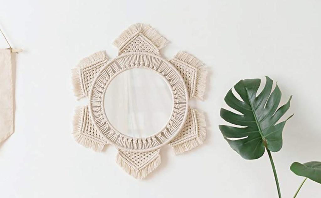 Macrame mirror on wall next to plant