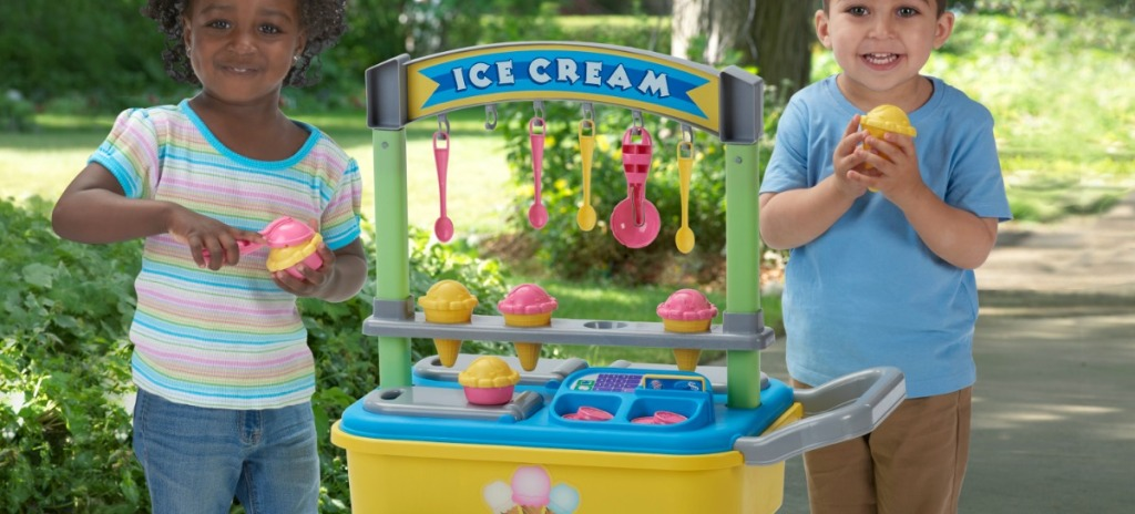two kids by plastic ice cream cart