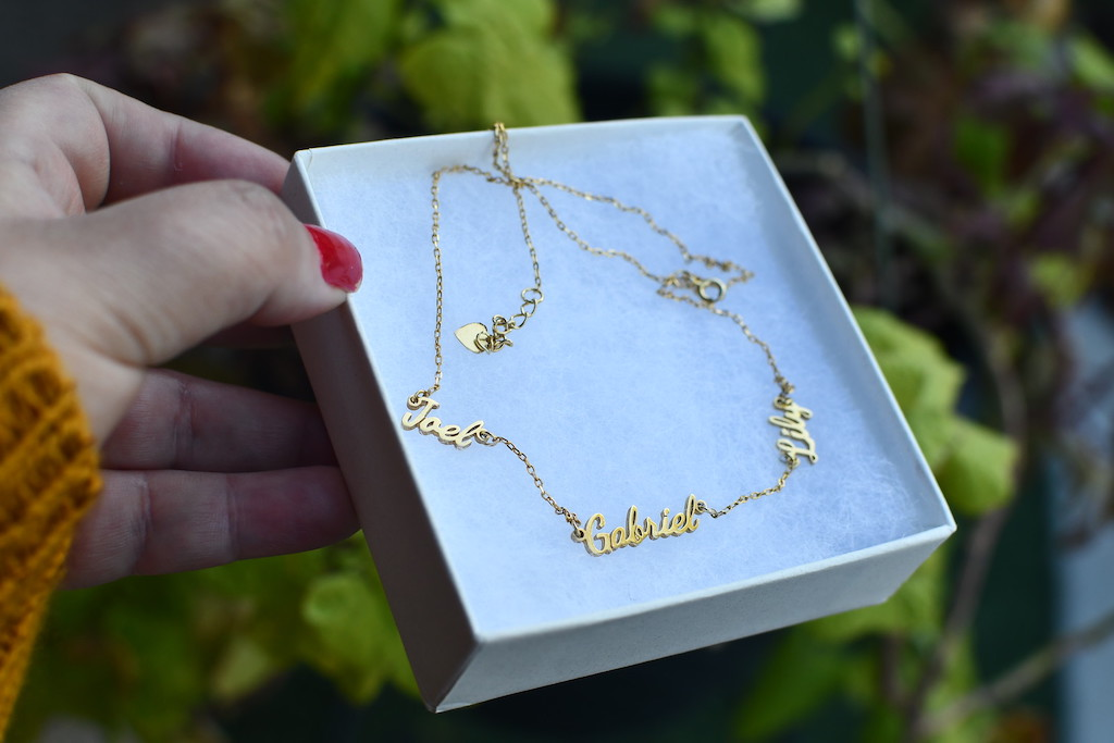 holding name necklace in box