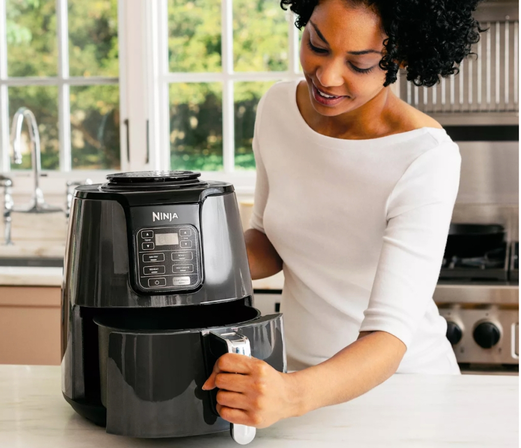 woman holding bottom of ninja air fryer in kitchen