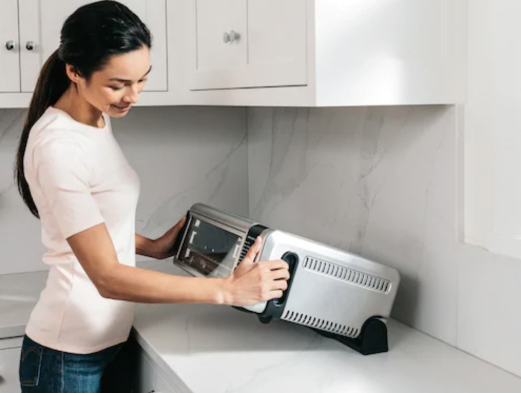 woman holding stainless steel air fryer on kitchen counter