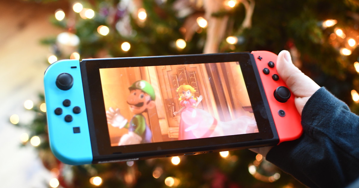 hand holding a nintendo switch toy in front of christmas tree