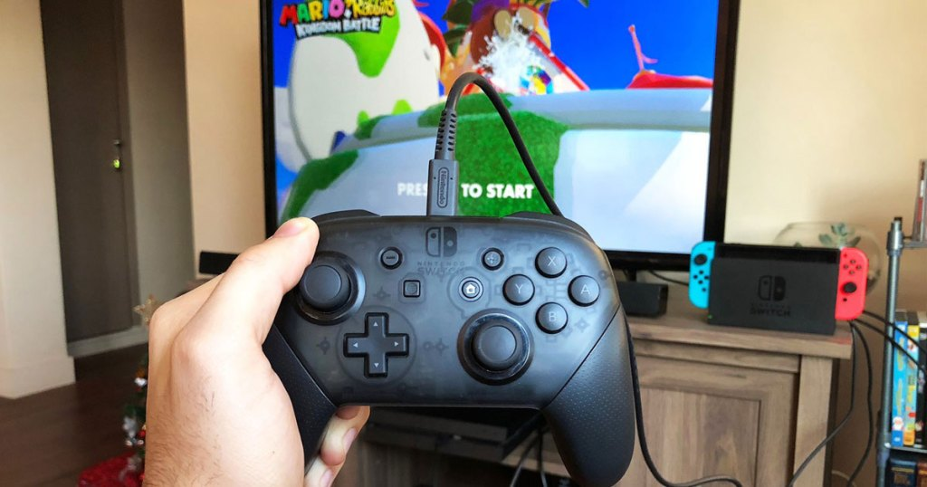 hand holding PowerA Controller for Nintendo Switch in front of tv