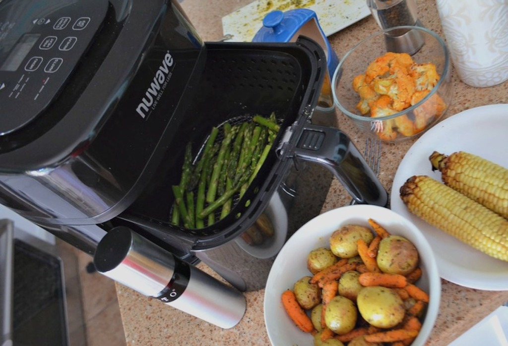 nuwave air fryer sitting on counter with cooked food