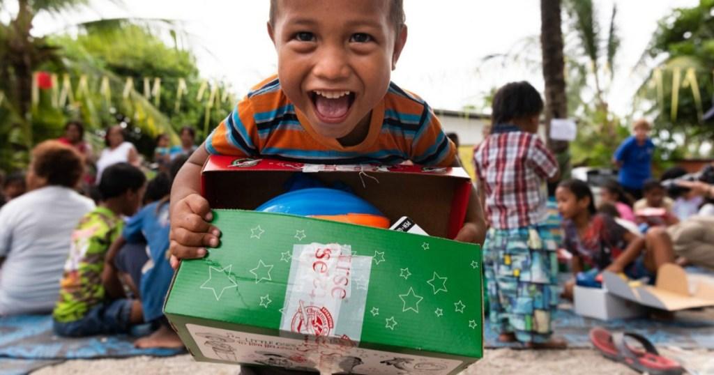 little boy holding Operation Christmas Child box