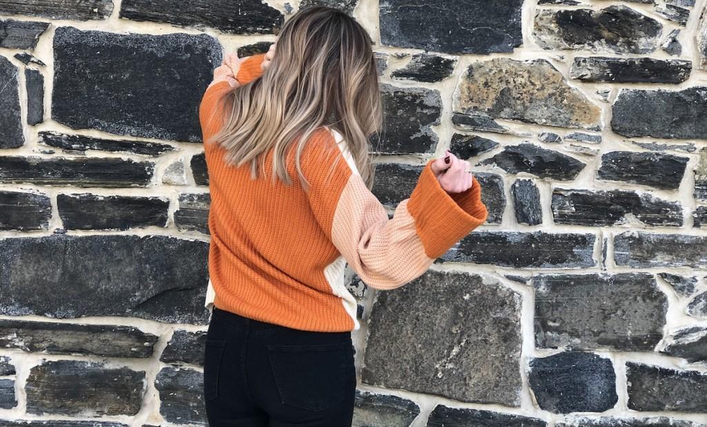 woman wearing orange colorblock sweater facing stone wall