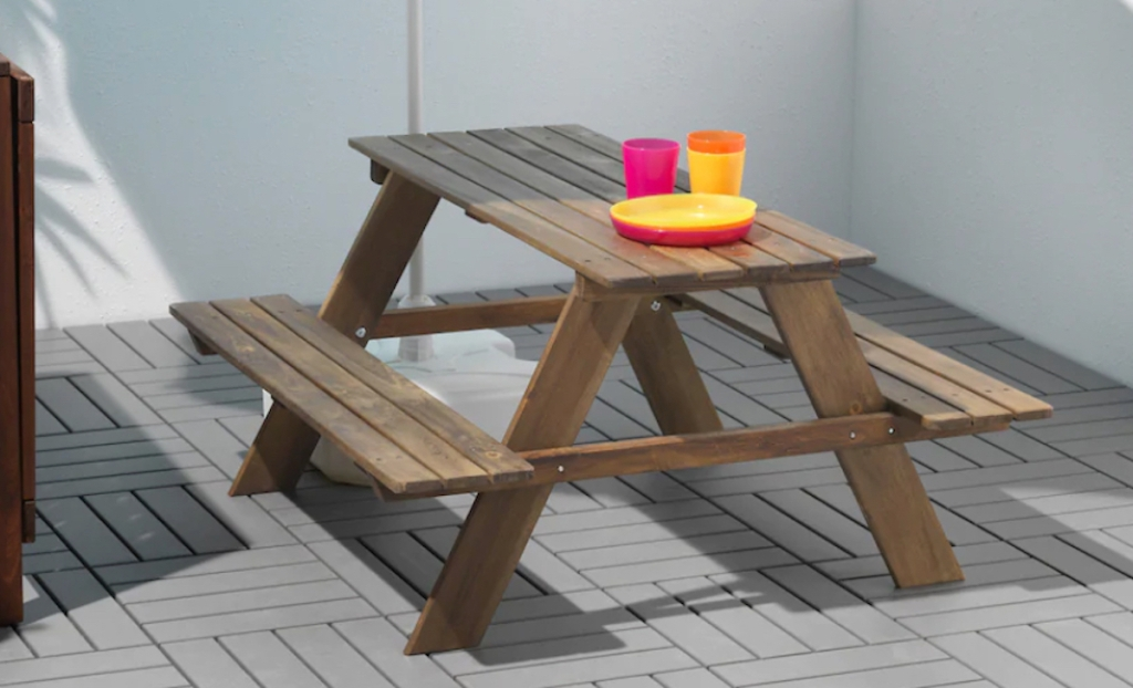 brown wood picnic table with bright colored dishes on top