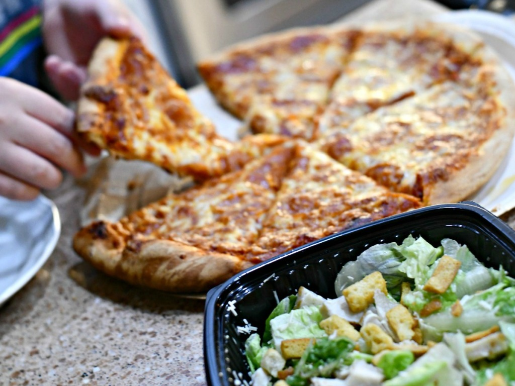 someone grabbing slice of pizza next to salad