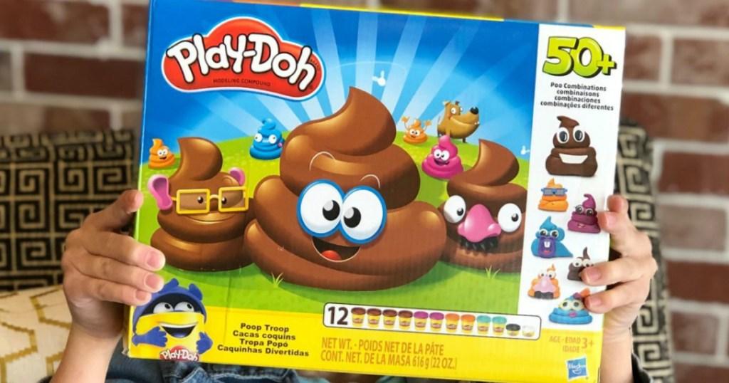 hands holding up play doh poop troop box