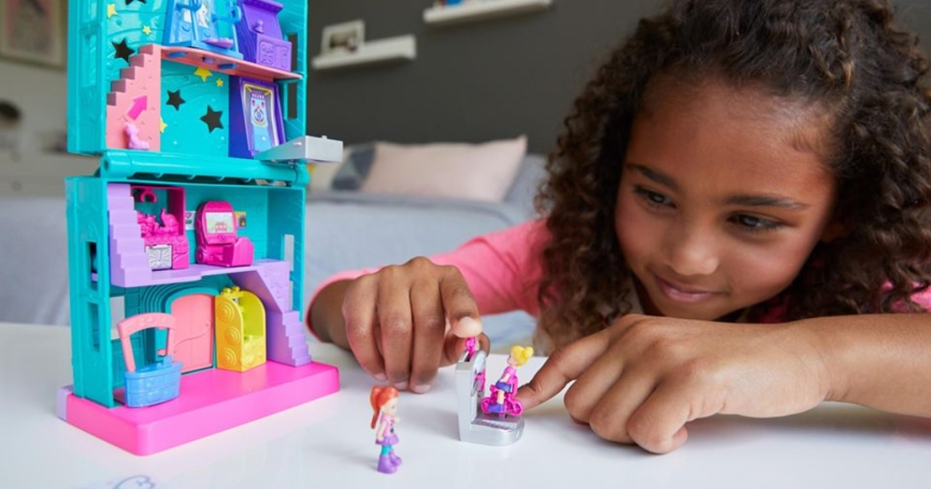 girl playing with Polly Pocket toys
