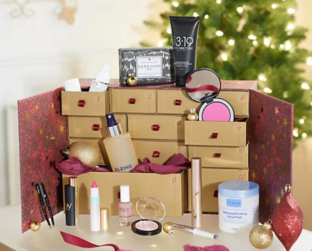 posh beauty advent calendar with products in drawers and christmas tree in background