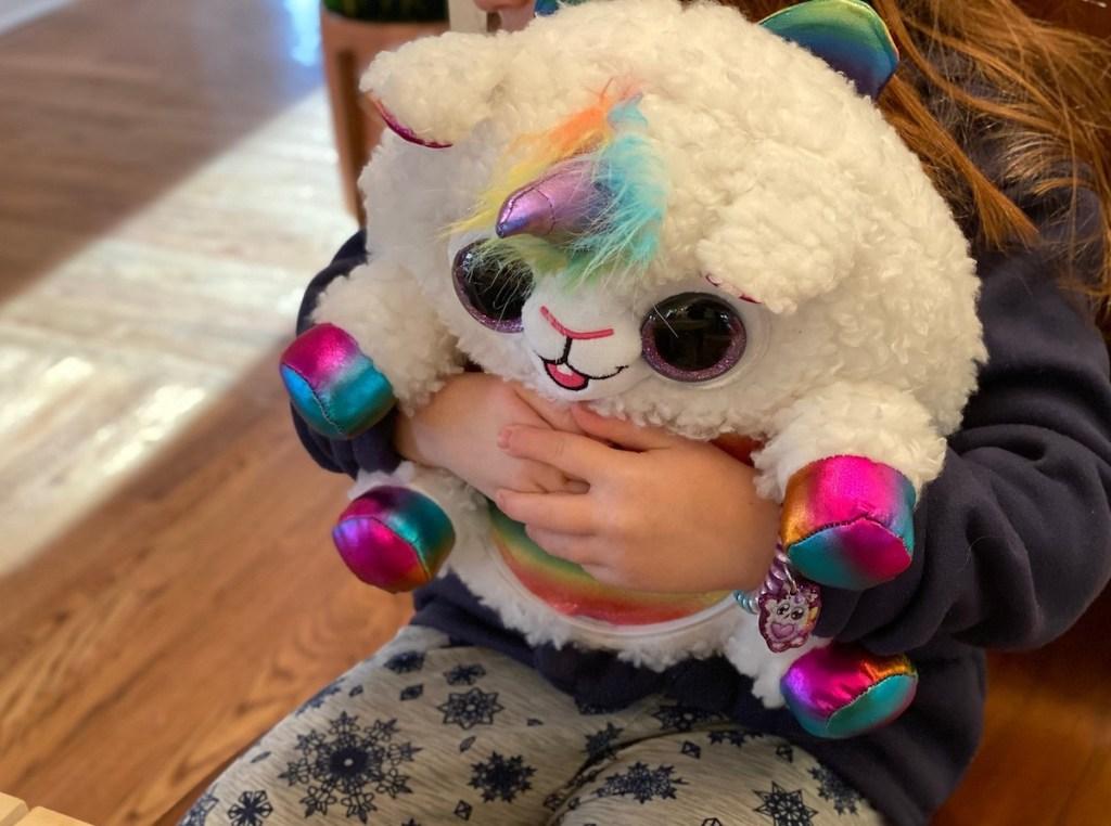 kid hugging plush rainbocorns stuffed animal