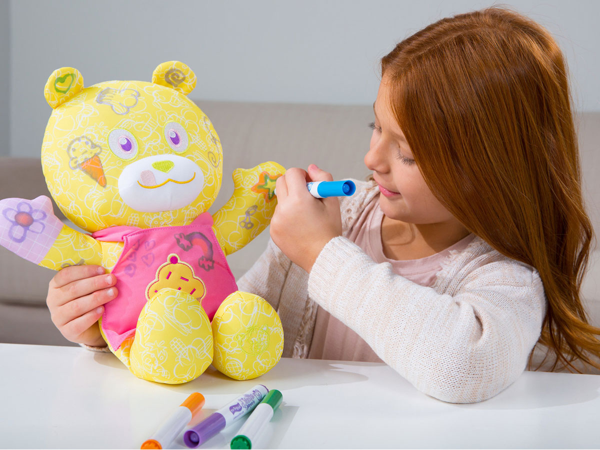 girl coloring on doodle bear yellow with markers