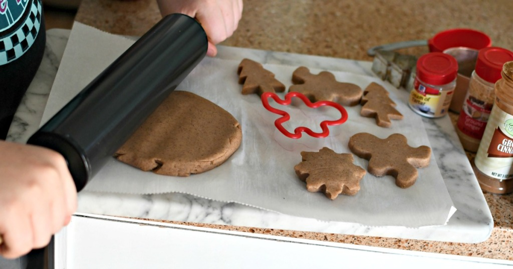 rolling gingerbread play dough on a cutting board