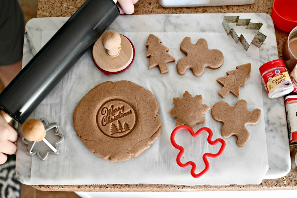 rolling out gingerbread play dough on a cutting board