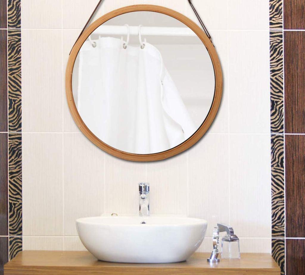 round mirror hanging over white bathroom sink