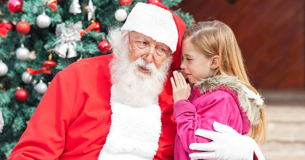 santa and little girl whispering christmas wishes to him