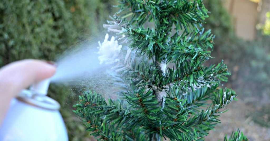 spraying fake snow on mini artificial Christmas tree
