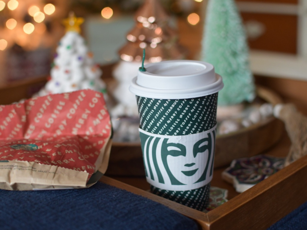 starbucks drink and food bag with christmas lights in background