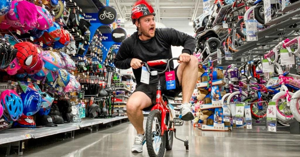 man wearing bike helmet riding bike in Walmart store