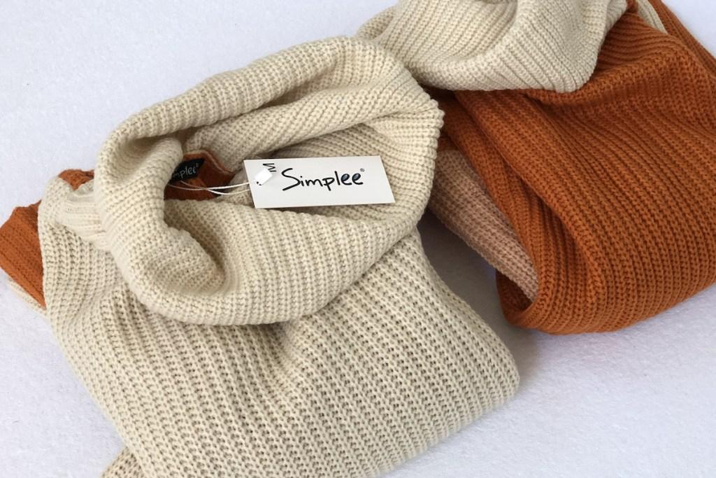 beige and orange sweaters folded