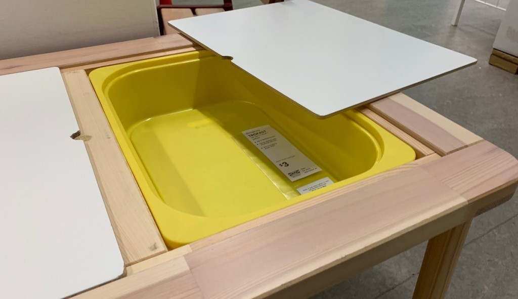 open table top with yellow plastic bin inside