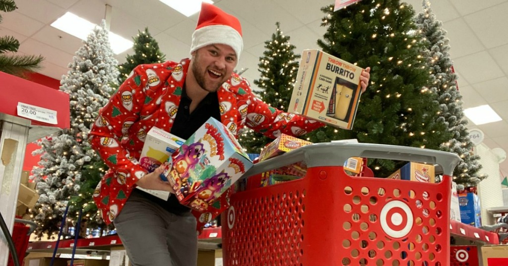 man with santa hat on holding board games at Target by shopping cart