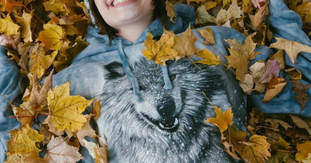 woman laying in leaves with wolf sweatshirt