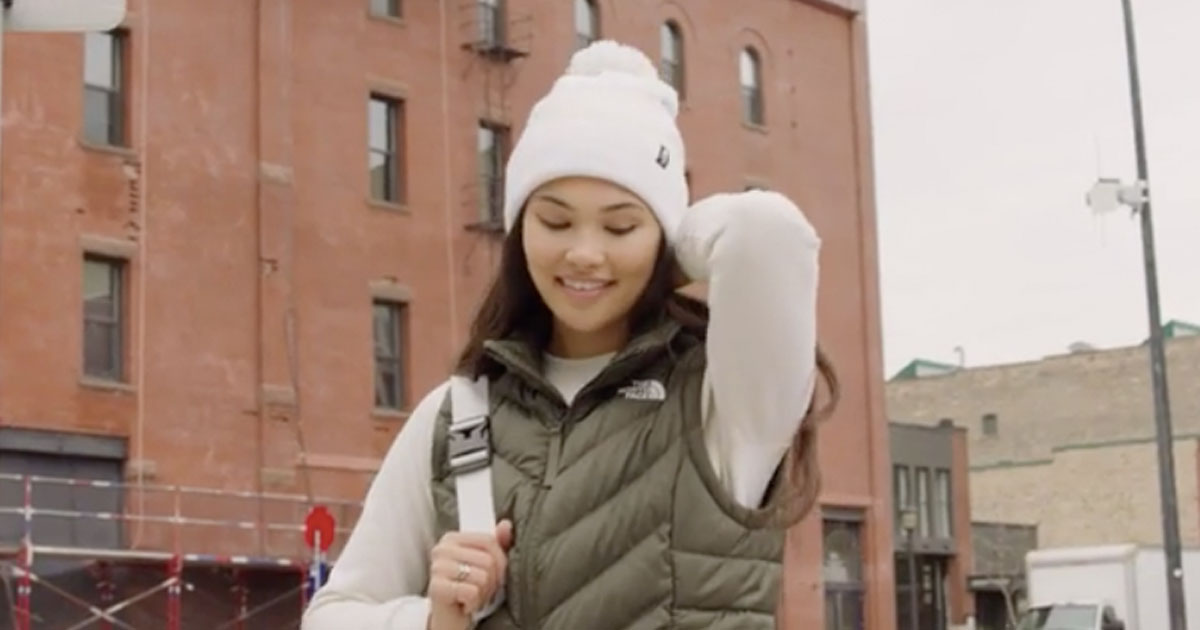 Woman standing outside of a building in the cold wearing a The North Face vest
