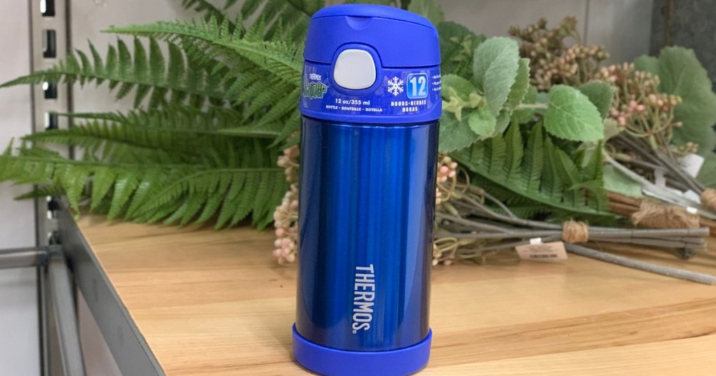 blue thermos sitting on counter with flowers in background
