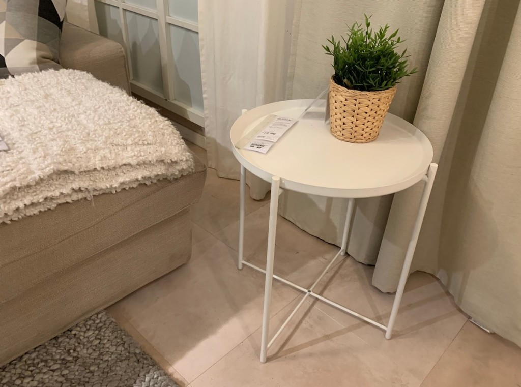 white tray table with small green plant on top next to bed