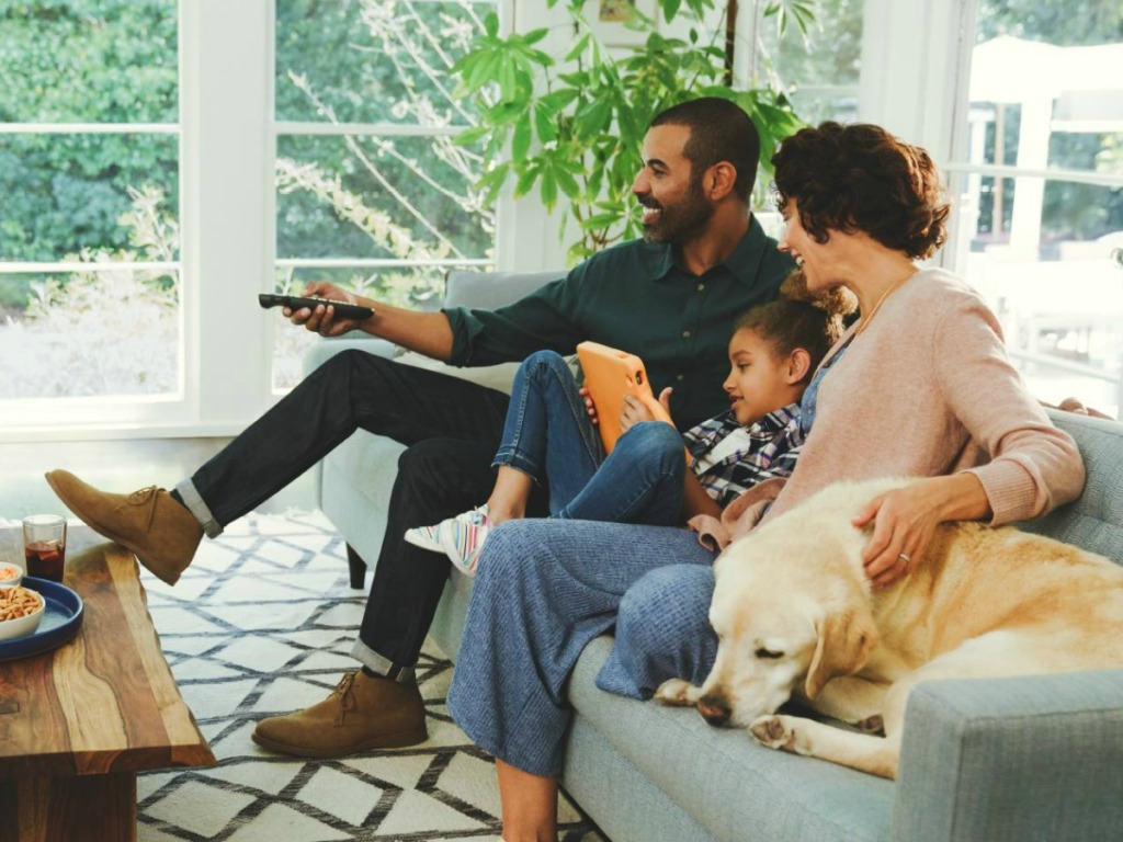 family watching tv sitting on couch with dog