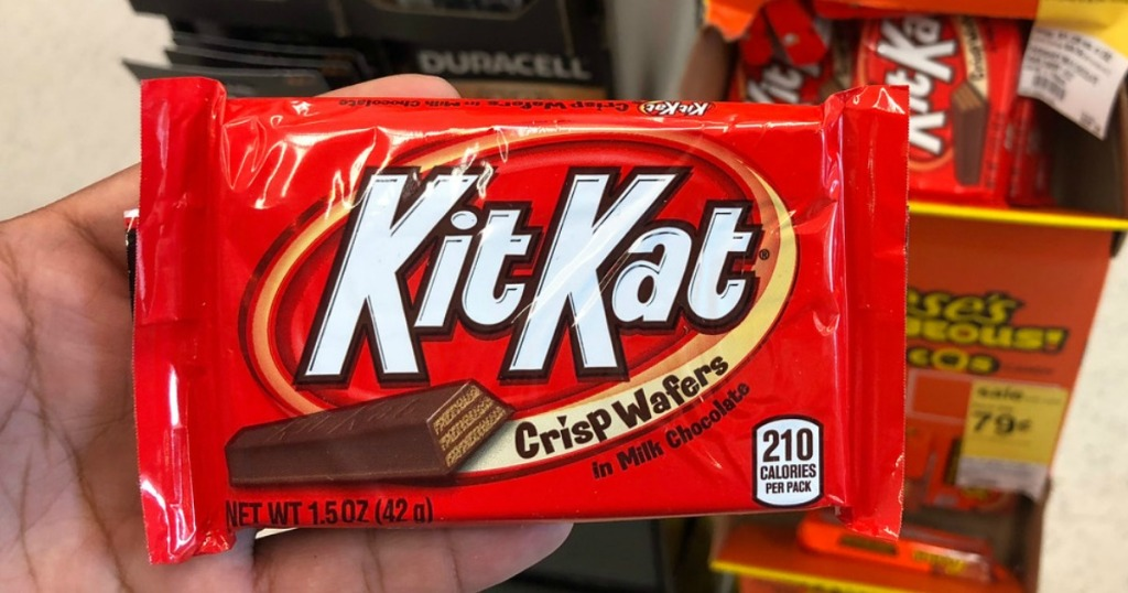 hand holding kit kat candy bar in a store