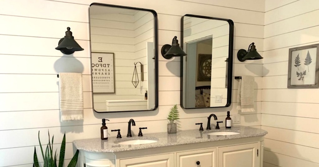 black wall mirrors hanging on white shiplap in bathroom