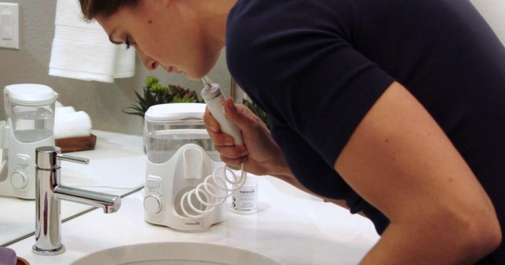 woman using waterpik in bathroom