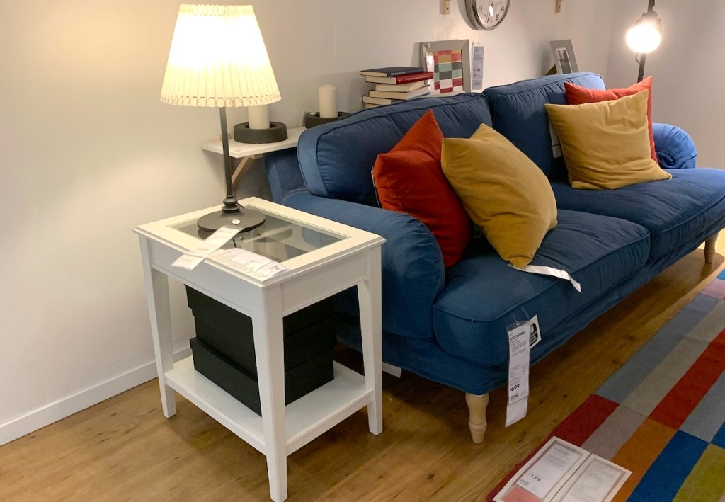 white side table next to blue couch and light lamp on top