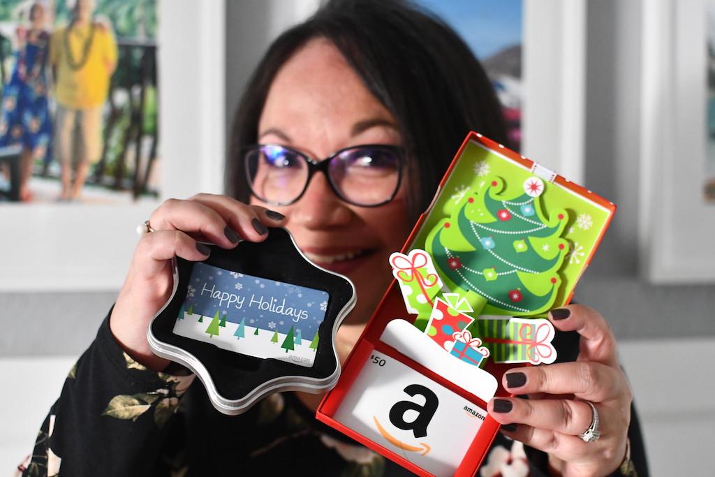 woman holding Amazon Christmas gift cards