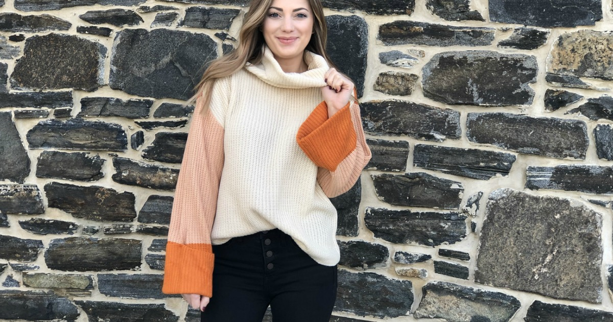 woman wearing orange and cream sweater with bell sleeves