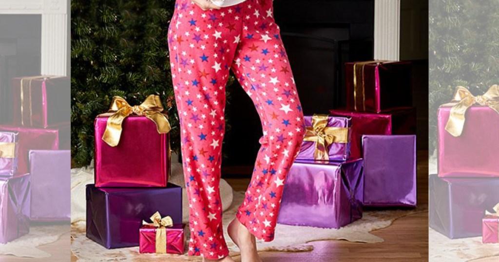 Women wearing PJ Pajama Bottoms next to Christmas tree and presents
