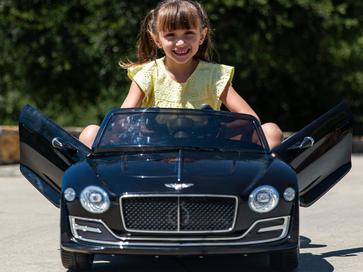 girl riding in ride-on car with doors open