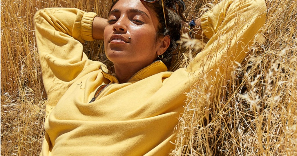 woman laying in a field wearing a Aerie Sunday Soft Quarter Zip Sweatshirt