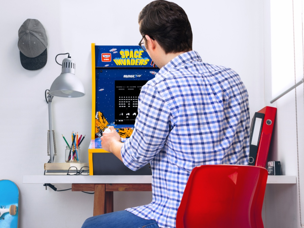 man playing space invaders counter arcade machine