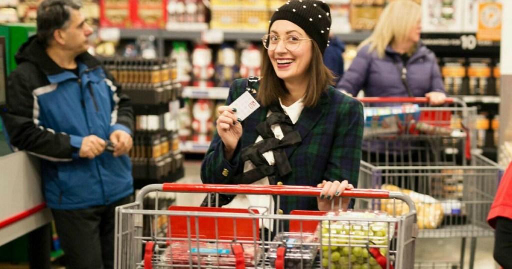 Woman holding BJs_Wholesale_Club_membership card and pushing cart