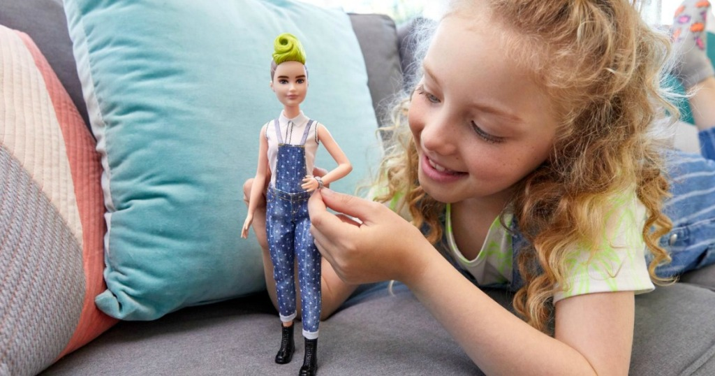 Young girl playing with a Barbie Fashionista doll on the sofa