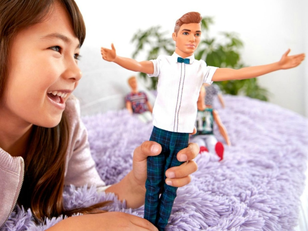 Young girl playing with a Ken doll that is wearing a bowtie