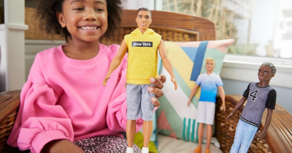 Young girl playing with a three Ken dolls from Barbie Fashionista Collection