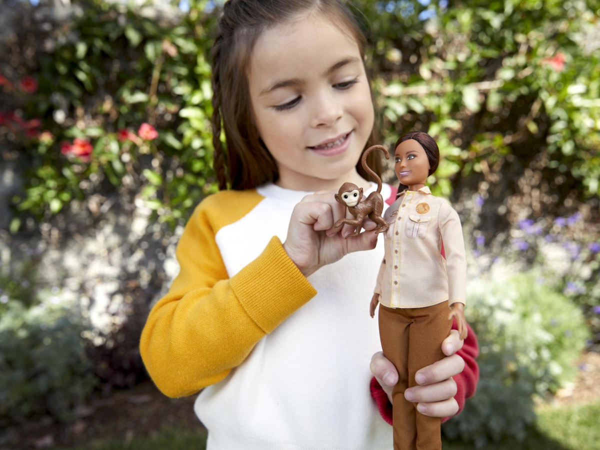 little girl playing with barbie outdoors