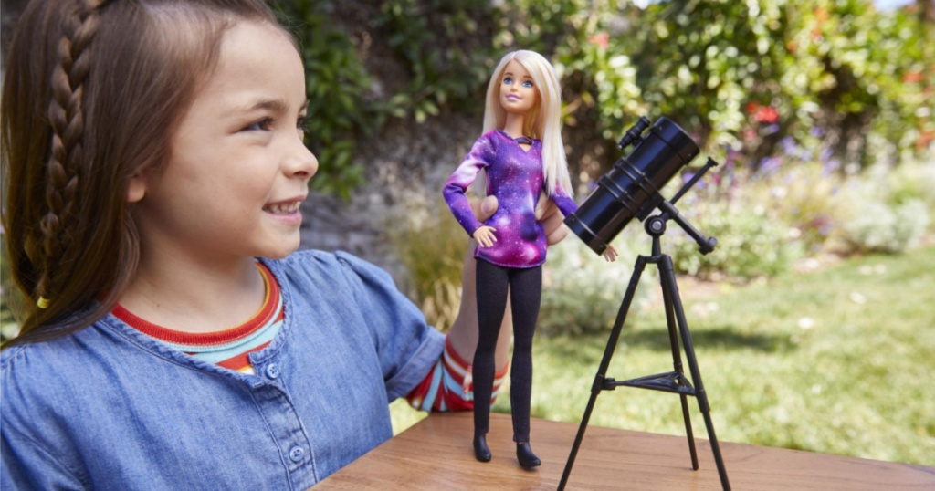little girl playing with barbie outside